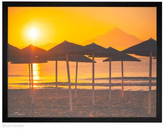 Морски плаж с чадъри по изгрев слънце, фотография
